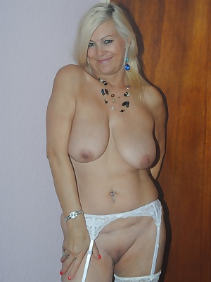 Platinum Lady dressed only in only her stockings and suspender shows off her geourgus mature tits and fingers her damp s