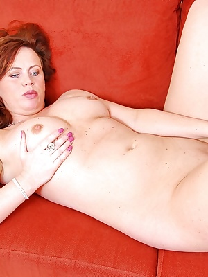 Horny redhead milf Dede is laying full nude and bare feet on her couch.She has some favorite sex toys she likes to show