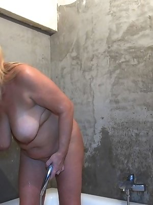 Lovely mature woman trying some toy after getting wet in the shower