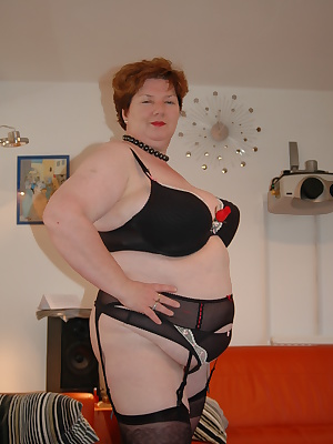 Black sheer nylon stockings, plus a matching suspender belt and big full black 44g bra with pink and cream detailing for