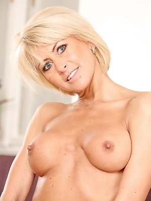 Mature blonde Cathie with big tits fingers her wet pussy on her knees
