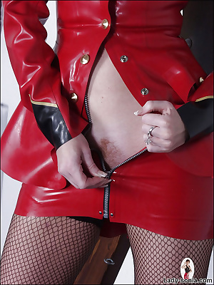 Filthy mature fetish lady in latex suit uncovering her petite ass
