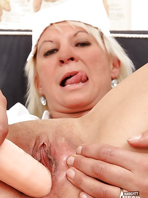 Salacious mature nurse revealing her shaved cunt and stuffing it with a toy