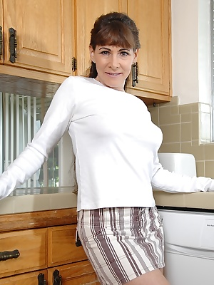 Busty aged lady Alexandra Silk slipping undies over pierced cunt in kitchen