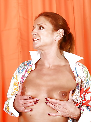 Redheaded mature Euro domme Lady Sarah exposing pierced pussy