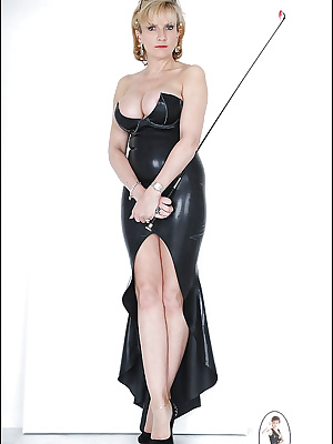 Deep-bosomed mature lassie posing in latex dress with very low neckline