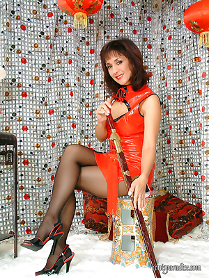Mature babe Roni posing in a red latex dress and black pantyhose